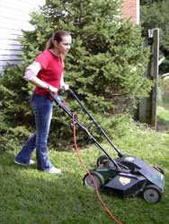girl cuts grass with electric mower